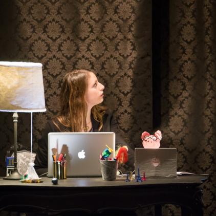 """La marionnettiste à son bureau, en conversation avec le portrait d'Haussmann, et le """"cochon-tirelire"""""""